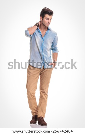 Attractive fashion man walking on studio background with one hand in his pocket while looking away from the camera. - stock photo