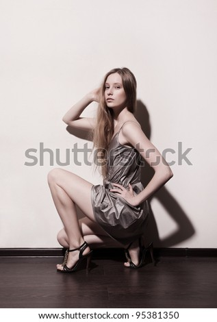 Attractive fashion model posing in studio and looking to the camera on light background