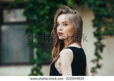 Attractive fashion woman in orange dress  posing near white house - stock photo