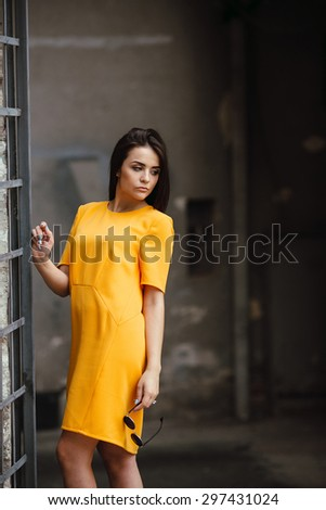 Attractive fashion woman in orange dress  posing near white wall - stock photo