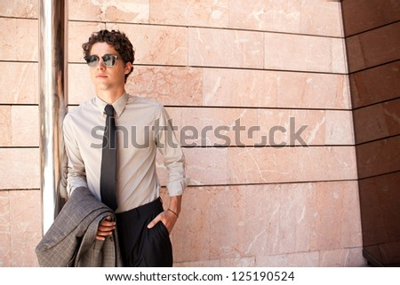 Attractive fashionable businessman wearing an elegant suit and shades, leaning on a metallic pole in a modern stone office building in the city.