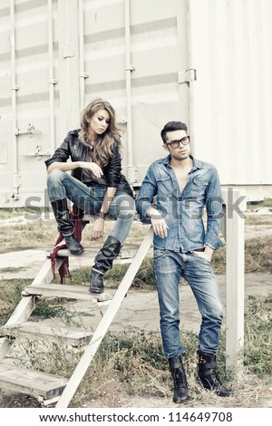 attractive fashionable couple wearing jeans posing dramatic - retro processed image - stock photo