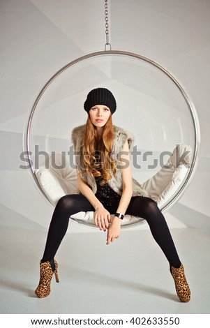 Attractive fashionable woman in black clothes sitting in hanging chair - stock photo
