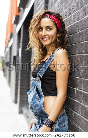Attractive fashionable young woman in dungarees leaning against a wall and smiling at something off camera - stock photo