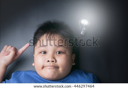 Attractive fat boy gets brilliant idea under bright bulb lamp with low key tone. - stock photo