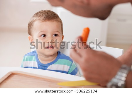 Attractive father is holding a carrot and a knife in his hands. He is giving vegetable to his child carefully. The toddler is looking at him with interest and smiling. The boy is sitting at the table - stock photo