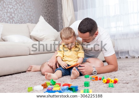 Attractive father is sitting near his little son on flooring. The boy is holding a mobile phone. They are looking at it with interest