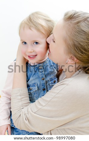 Attractive female and her daughter sharing secrets. - stock photo
