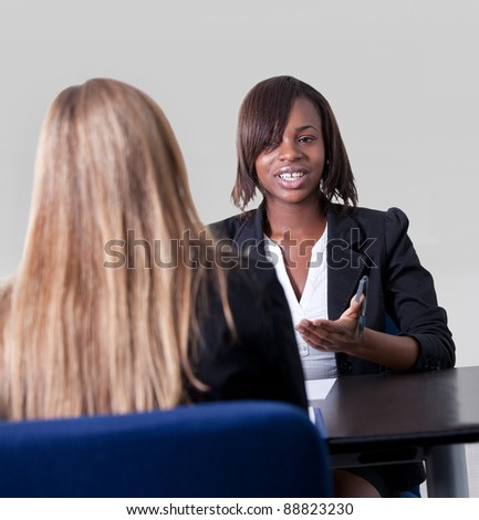 Attractive female applicant showing documents and replying questions to the manager at a job interview