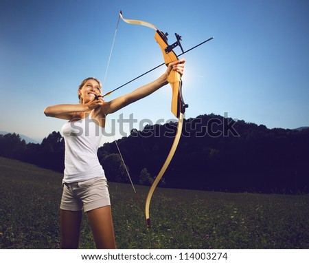 Attractive female archer bending a bow and aiming in the sky - stock photo