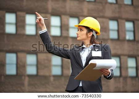 attractive female architect in yellow hard hat point to building, grey suit and shirt - stock photo