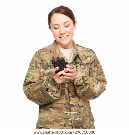 Attractive female Army soldier looking down at her cell phone on a white background. - stock photo