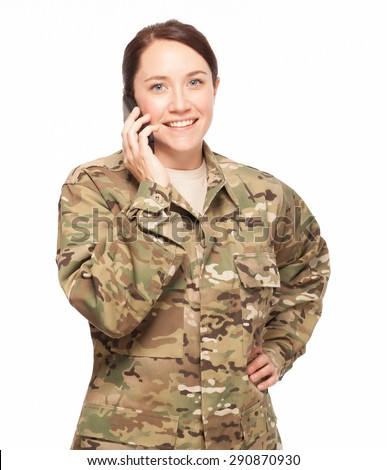 Attractive female Army soldier wearing multicam camouflage on her mobile cell phone. - stock photo