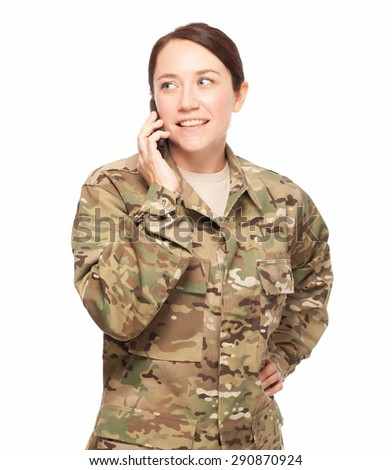 Attractive female Army soldier wearing multicam camouflage on her mobile cell phone, looking away. - stock photo