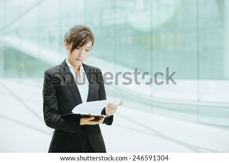Attractive female Asian business executive in a stylish jacket standing holding a clip board in front of a cool toned reflection on an urban building facade, with copyspace