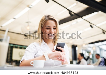 Attractive female at a cafe, using her phone and wearing smartwatch.