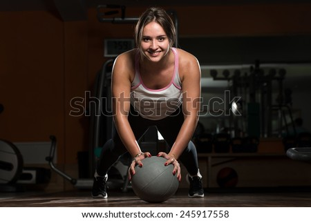 Attractive Female Athlete Performing Push-Ups On Medicine Ball - stock photo