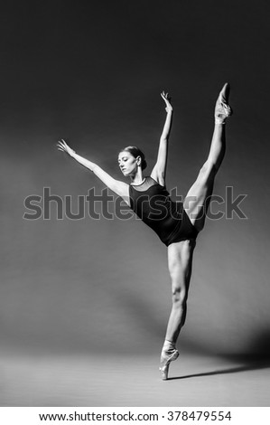 Attractive female ballet dancer in black custome and ballet shoes dancing in studio. Grayscale image. - stock photo