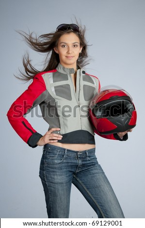 Attractive female biker with fly-away hair, dressed in jacket and holding red motorbike helmet. - stock photo