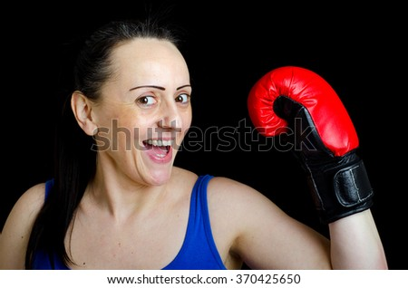 Attractive female boxer happy after victory. Black background.