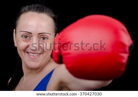 Attractive female boxer smiling while throwing punch. Black background - stock photo