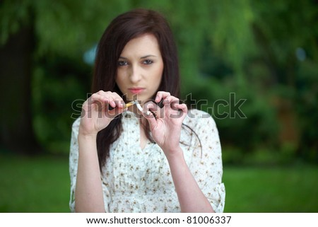 attractive female breaks cigarette, refuse to smoke - stock photo