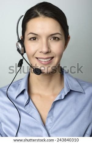 Attractive female call center operator, client services assistant or telemarketer wearing a headset looking at the camera with a charming friendly smile, on grey with copy space - stock photo
