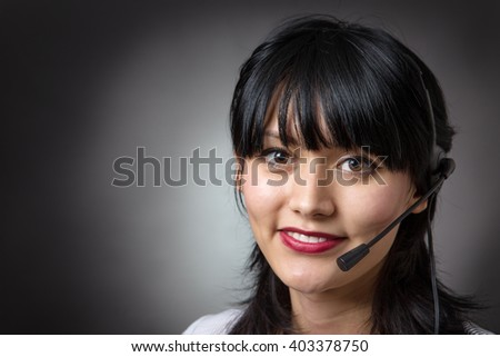 Attractive female call center operator, client services assistant or telemarketer wearing a headset looking at the camera with a charming friendly smile, shot on a grey background. - stock photo