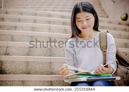 attractive female college student sitting on stairs - stock photo