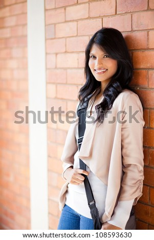 attractive female college student standing by the wall - stock photo