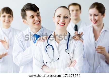 Attractive female doctor in uniform congratulated by colleagues