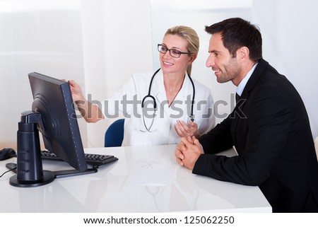 Attractive female doctor sitting at her desk pointing to a computer screen explaining something to a male patient - stock photo