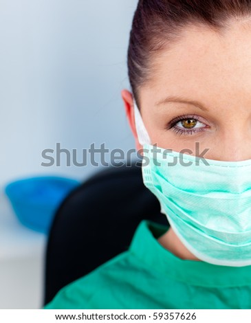 Attractive female doctor with scrubs and mask in a hospital looking at the camera - stock photo