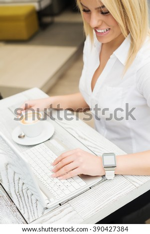 Attractive female drinking coffee and surfing internet at cafe bar.