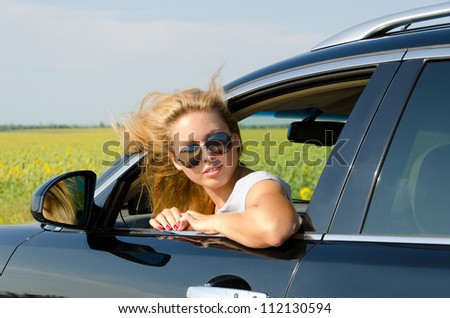 Attractive female driver with sunglasses looking through window of her car
