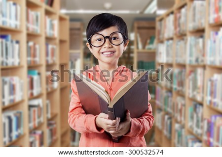 Attractive female elementary school student reading a literature in the library and smiling on the camera - stock photo