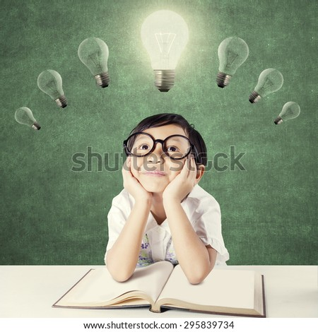 Attractive female elementary school student with a textbook on the table, thinking idea while looking up at bright light bulb - stock photo