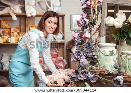 Attractive female florist is making a bouquet with inspiration. She is standing in her workshop and smiling. The lady is looking at the camera happily - stock photo