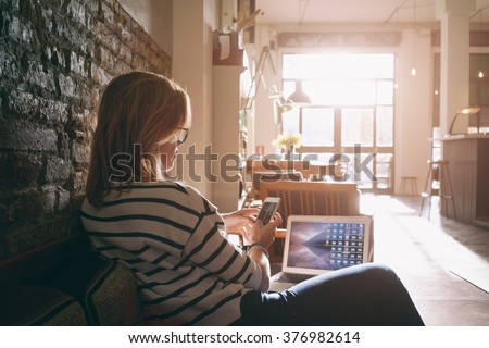 Attractive female freelancer chatting with her friends  while sitting front open computer in vintage coffee shop - stock photo