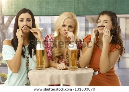 Attractive female friends having fun, forming moustache from hair, drinking beer. - stock photo