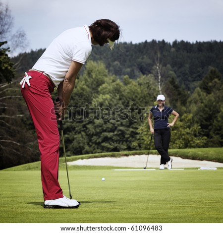 Attractive female golf player putting on green with second player in the background. - stock photo