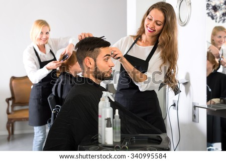 Attractive female hairdresser is making a haircut for a handsome male customer in a barbershop indoors - stock photo