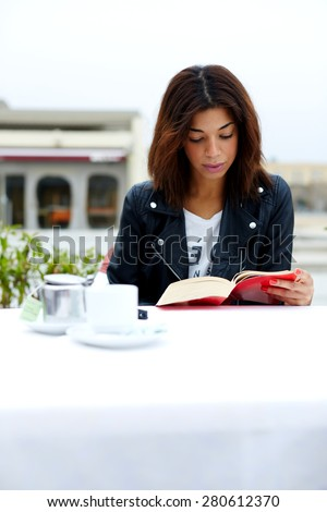 Attractive female hipster enjoying a good book in cafe during her recreation time at weekend, lovely young woman read novel sitting at the table of coffee shop, student engage leisure time for reading - stock photo