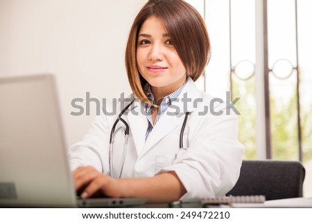 Attractive female Hispanic doctor using a laptop computer at her office and smiling - stock photo