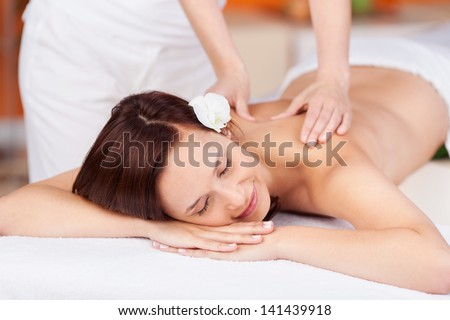 Attractive female is getting a relaxing massage - stock photo