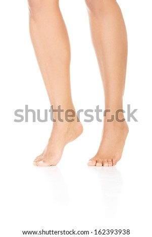 Attractive female legs. Vertical. Isolated on white.