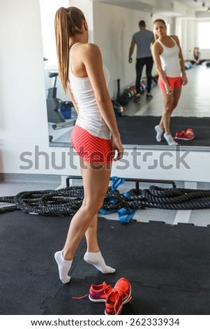 Attractive female looking on her reflection in mirror at gym - stock photo