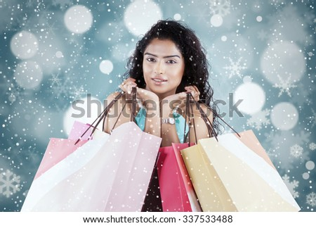 Attractive female model smiling at the camera while carrying shopping bags with winter background - stock photo