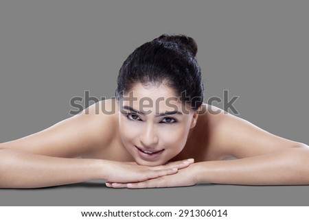 Attractive female model with fresh skin relaxing in studio while smiling at the camera - stock photo