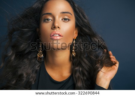 attractive female model with long curly black hair and bright makeup. Beauty and fashion portrait.Toned in warm colors, studio shot on blue background. horizontal. - stock photo